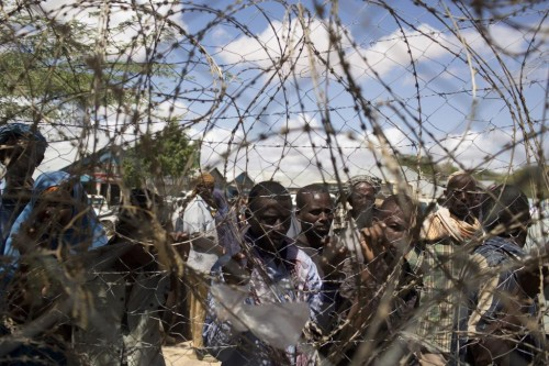 Somali refugees look through a barbwire fence of a United Nations World Food Programme distribution centre during a food distribution exercise in Dagahale, one of the several refugee settlements in Dadaab, October 8, 2013.  REUTERS/Siegfried Modola