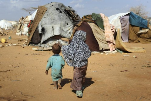 "Children walk together amongst makeshift homes, or ""tukuls"", in the outskirts of Dagahaley settlement at Kenya's Dadaab Refugee Camp, August 31, 2011. REUTERS/Jonathan Ernst"