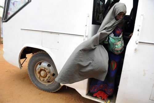 A Somali refugee woman carrying a baby disembarks from a bus at the Ifo reception center at Kenya's Dadaab Refugee Camp, September 1, 2011. REUTERS/Jonathan Ernst