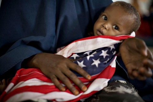 "A malnourished Somali child is wrapped in an American ""Stars and Stripes"" cloth at a therapeutic feeding center at Dagahaley camp in Dadaab, June 8, 2009.  REUTERS/Finbarr O'Reilly"