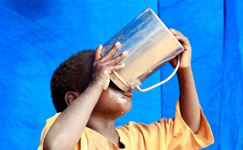 A newly arrived refugee child drinks inside their tent in Baley settlement near the Ifo extension refugee camp in Dadaab, July 27, 2011.  REUTERS/Thomas Mukoya