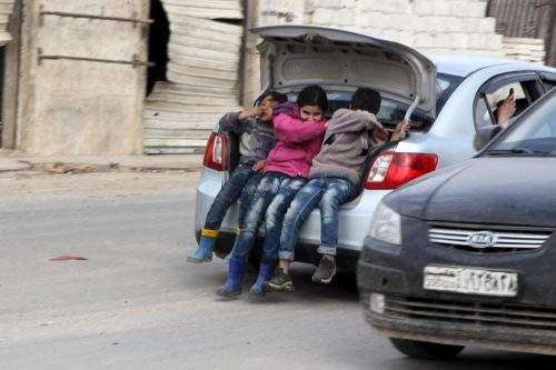 Children ride in the trunk of a car in Kafr Hamra village, northern Aleppo countryside, Syria February 27, 2016. REUTERS/Abdalrhman Ismail