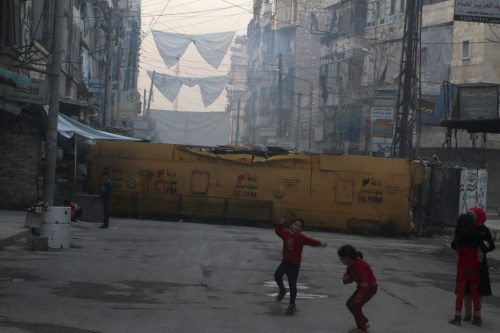 Children play near a bus barricading a street, which serves as protection from snipers loyal to Syria