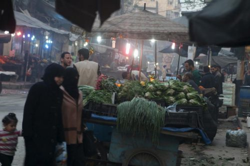 Women walk near displayed produce in a vegetable market in Aleppo