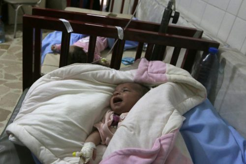 Babies lie on beds after being transferred to an underground unit at a children