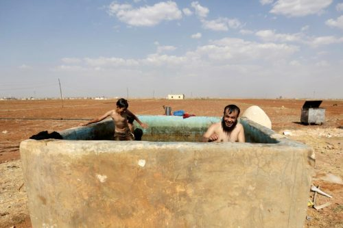 An Al-Furqan Brigade fighter (R) swims inside an irrigation pool with local children to cool down from summer heat, in Tel Mamo village, in the southern countryside of Aleppo, Syria June 23, 2016. REUTERS/Khalil Ashawi