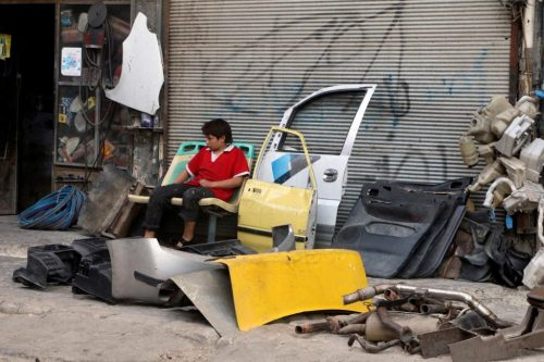 A boy rests near car parts in the rebel held al-Katerji district in Aleppo, Syria August 13, 2016. REUTERS/Abdalrhman Ismail