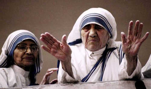 Mother Teresa blesses reporters and photographers gathered in the courtyard of the headquarters of her Missionaries of Charity in the eastern Indian city of Calcutta as Sister Nirmala looks March 14, 1997. REUTERS