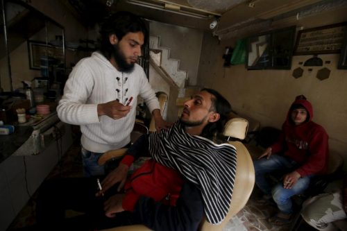 A barber attends to a customer in a rebel held area of the old city of Aleppo, Syria March 27, 2016. REUTERS/Abdalrhman Ismail