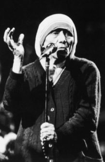 Mother Teresa raises a hand as she speaks to a large crowd in Vancouver