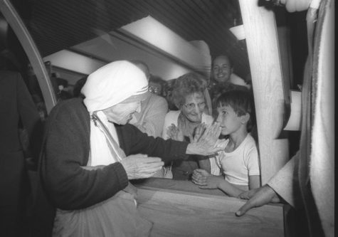Mother Teresa touches the protective window towards the face of a young child who was among the hundreds who came to greet her at the Quebec Airport, June 10, 1986. Reuters/Jacques Boissinot