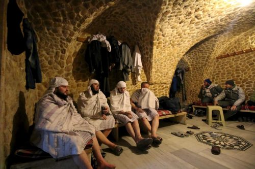 Customers rest after taking a steam bath at al-Salhiyeh traditional hammam, at a rebel-controlled area in the old city of Aleppo, Syria January 26, 2016. Al-Salhiyeh traditional hammam reopened its door after four years of closure. REUTERS/Abdalrhman Ismail