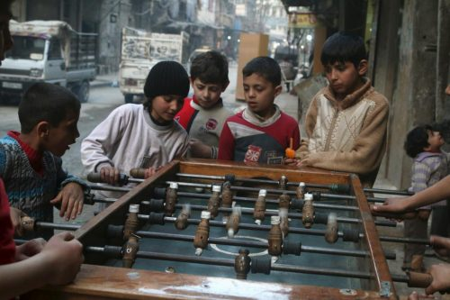Children play table football in Aleppo