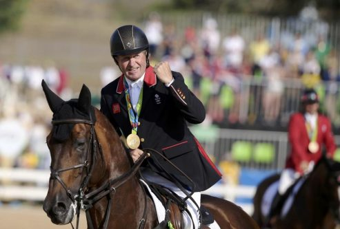 Nick Skelton of Britain on his horse Big Star celebrates his gold medal. REUTERS/Tony Gentile