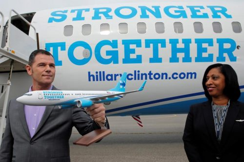 Michael Hackert, vice president at Xtra Airways, holds a model of Hillary Clinton's campaign plane in front of the real thing at the Westchester County Airport. REUTERS/Brian Snyder