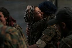 Syria Democratic Forces (SDF) female fighters embrace each other in the city of Manbij, in Aleppo Governorate