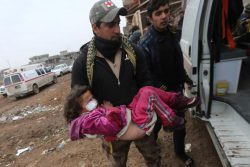 An Iraqi soldier carries a girl who was wounded during clashes in the Islamic State stronghold of Mosul into a field hospital in al-Samah neighborhood Iraq