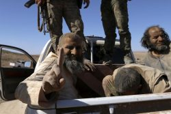One of the three men that Democratic Forces of Syria fighters claimed were Islamic State fighters gestures while being held as a prisoner near al-Shadadi town
