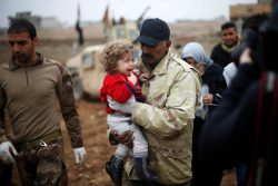 An Iraqi soldier carries a girl, who fled the Islamic State stronghold of Mosul, in al-Samah neighborhood