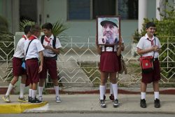 Children stand along a street while waiting for the ashes of Fidel Castro to pass in Cardenas