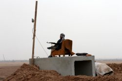 A Kurdish Peshmerga fighter looks over Mosul from his position near Abu Jarboa village