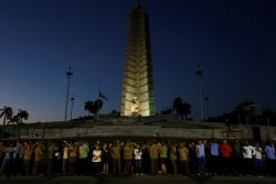 People wait to see a military vehicle transport the ashes of Cuba's late President Fidel Castro in Havana