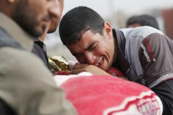 A man cries over a body of a baby killed by a mortar round fired by Islamic State fighters in Mosul