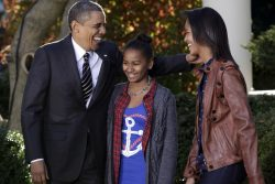 U.S. President Barack Obama laughs with his daughters Sasha and Malia as he pardons National Thanksgiving Turkey, Cobbler, in The Rose Garden of the White House in Washington
