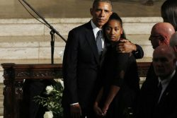 U.S. President Obama hugs daughter Sasha as the casket of former Delaware Attorney General Beau Biden, son of Vice President Biden, leaves his funeral in Wilimington, Delaware