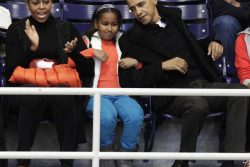 President Barack Obama with the first family watches a basketball game in Washington